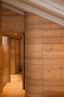 Built-in cupboards in new wood follow the contours of the landing