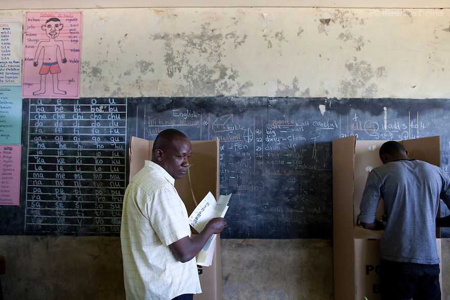 4 March 2013 - Nairobi, Kenya - Two Kenyan men cast their ballots at a polling centre during the Kenyan general elections in Nairobi, Kenya. Five years after more than 1,000 people were killed in election-related violence, Kenyans began casting votes in a nationwide election seen as the country's most important, and complicated, in its 50-year history. Uhuru Kenyatta, one of two top candidates for president, faces charges at the International Criminal Court for orchestrating the 2007-08 postelection violence. Photo credit: Benedicte Desrus