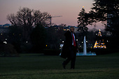 United States President Donald J. Trump holds his hand to his ear as he crosses the South Lawn of the White House while the press shouts questions at him as he returns from visiting wounded service members at Walter Reed Military Hospital on December 21st, 2017 in Washington, D.C. Credit: Alex Edelman / CNP