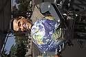 A robot with a smiling Arnold Schwarzenegger mask holds a globe of planet earth in his hands. Contact Green Stock Media to view additional images from this photo shoot. ..Image size: 4368 x 2912 pixels, very high resolution, 12.8 megapixels