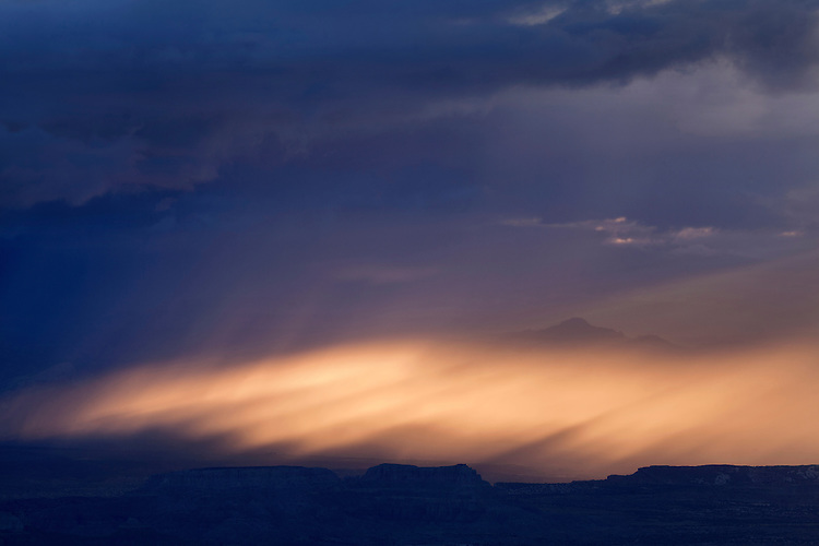 Monsoon storm over Capital Reef National Park near sunset creates spectacular light beams as viewed from the Henry Mountains in southern Utah, USA