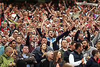 Pictured:Ecstatic Swansea supporters celebrating their team's win after the final whistle. Saturday 16 August 2014<br />