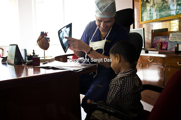 58 year old heart surgeon, Dr. Devi Prasad Shetty shares a light moment with a young patient during OPD in his office at the Narayana Hrudayalaya in Bangalore, Karnataka, India. Photo: Sanjit Das/Panos