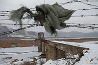 A piece of clothing is used to make a gap in barbed wire near the closed bridge over the Yalu river, on the Chinese side of the border with North Korea between towns of Linjiang and Ji'an November 21, 2017.   REUTERS/Damir Sagolj
