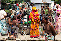 River fishermen sell freshly caught fish just outside the meeting hut of a Children's Group in Bhashantek Basti (Slum) in Zon H, Dhaka, Bangladesh on 23rd September 2011. The Bhashantek Basti Children's Group is run by children for children with the facilitation of PLAN Bangladesh and other partner NGOs. Slum children from ages 8 to 17 run the group within their own communities to protect vulnerable children from child related issues such as child marriage. About 20150 people live in the Bhashantek urban slum, with an average household size of 5 in housing sizes of 8 x 9ft made of bamboo, tin sheets and scrap materials. The average annual income is USD 200. Photo by Suzanne Lee for The Guardian