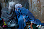 Two burqa-clad students whisper during the lesson at a school in a private residence in Kandahar, Afghanistan, Tuesday morning, April 20, 2009. Security concerns prompt the girls to wear burqas when outsiders visit. In hopes of increasing women's literacy, a joint Canadian International Development Agency and World Food Program initiative exchanges a monthly ration of food for each student's attendance in the class. Deteriorating security and a shortage of schools for girls have prompted hundreds of discreet schools to spring up in Kandahari homes.