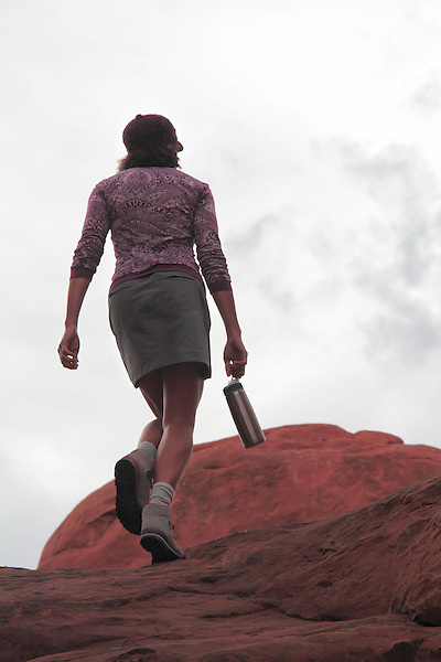 Woman walking on slickrock sandstone in Arches National Park, Moab, Utah, USA. .  John offers private photo tours in Arches National Park and throughout Utah and Colorado. Year-round.
