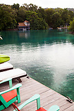 JAMAICA, Oracabessa. Bungalows and an outdoor porch at the Goldeneye Hotel and Resort.