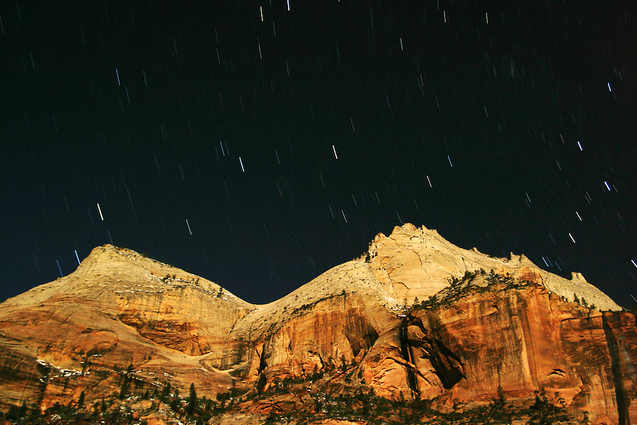 Star trails above canyon Walls lit by moon, Zion National Park, Washington County, UT