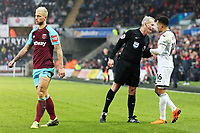 referee Martin Atkinson (C) speaks to Martin Olsson of Swansea City (R) after a challenge by Marko Arnautovic of West Ham (L) during the Premier League match between Swansea City and West Ham United at The Liberty Stadium, Swansea, Wales, UK. Saturday 03 March 2018