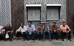 Palestinian employees paid by Palestinian Authority sit outside a Palestine Bank as they wait to receive their salaries, in Gaza city on June 5, 2014. A Palestinian unity government formed by President Mahmoud Abbas and the Islamist Hamas group faced its first and serious challenge on Thursday when civil servants of Hamas, who were not on the payment list, scuffled with those cashing their salaries. Civil servants employed by Hamas since 2007 arrived and prevented employees paid by the Palestinian Authority from receiving their salaries, vowing either both get paid or no one does. Photo by Ashraf Amra