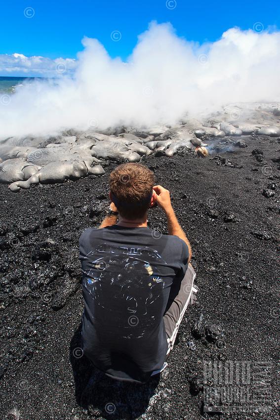 A man takes a photo of lava meeting the ocean at Fox's Landing black sand beach on the Big Island.