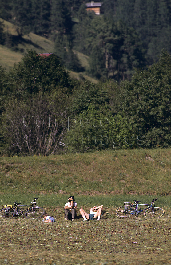 Cycling family resting in a field