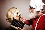 Santa Claus planning his route around the world December 25
