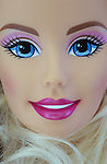 Close up of face of contemporary woman doll with stereotypical big blue eyes bright pink lips and long blonde hair