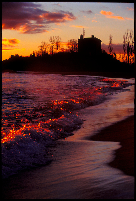 THE MARQUETTE LIGHTHOUSE IS SILHOUETTED AT DUSK AS LAKE SUPERIOR WAVES CRASH ON A BEACH IN MARQUETTE MICHIGAN.