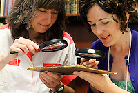 Jessica Henze, left, and Jennifer Evers, right, use a magnifying glasses to determine the type of leather used on a book cover during a Rare Book School summer camp book binding class held at the University of Virginia in Charlottesville, Va. The school hosts an annual summer camp for scholars and other professionals who work with rare books. Photo/Andrew Shurtleff