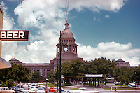 "Vintage view of the Texas State Capitol with ""Beer"" sign at the Capitol Tavern, favorite bar of the Texas Senate and Texas House of Representatives for drinking and negotiating legislation. Line of retro cars and trucks parked along the Capitol in July 1958 - Stock Image."