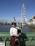 English man playing bagpipes near the London Eye in London, England.