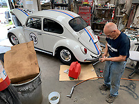 Paul Pitts, an automotive restorer and mechanic with Parker Motor Company in Fayetteville, polished a piece of trim Tuesday, July 28, 2020, while working on a 1967 Volkswagen Beetle in the company's shop in south Fayetteville. The car is made to look like Herbie from The Love Bug movies from the 1960s and 1970s and is being prepared for a collector car auction. Visit nwaonline.com/200729Daily/ for today's photo gallery.<br /> (NWA Democrat-Gazette/Andy Shupe)
