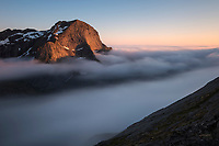 Midnight sun illuminates Storskiva mountain peak as it rises above coastal fog, Moskenesøy, Lofoten Islands, Norway