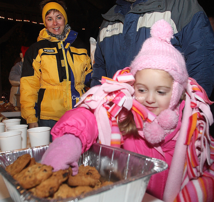 Ashley Hennessey digs into the cookies as her aunt Donna Hennessey looks on. Over a hundred children and their parents gathered at the Legion Pool in Seymour Saturday night to enjoy the hot chocolate and cookies and fireworks which signaled the arrival of Santa Claus at the Seymour Land Trust's 12th Annual Christmas Visit of Santa Claus.  Michael Kabelka / Republican-American