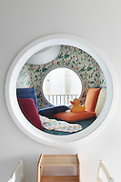A child's cabin, complete with cosy cushions and wallpaper, has been created in the bathroom with a porthole window overlooking the extension