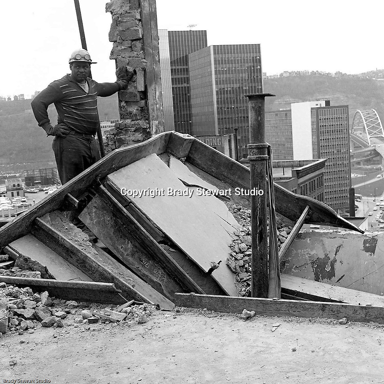 Pittsburgh PA:  Worker reviewing damage during the building demolition of one of downtown Pittsburgh's grand department stores, Rosenbaums. Gateway Center 4, State Office Building and Fort Pitt Bridge in background. Located at Penn Avenue and Sixth Street in Pittsburgh, the store closed in 1960 and taken down in 1963 to make way for the Sixth Avenue garage.  The demolition work was completed by D&H Building Wreckers.