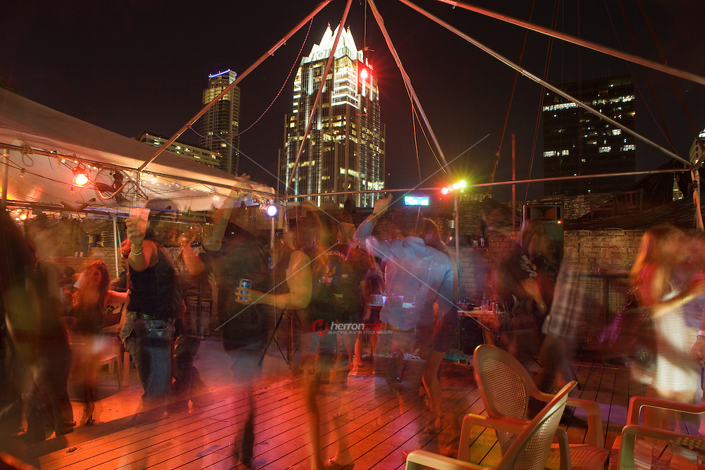 Group of friends dance and party at a rooftop bar on 6th Street in Austin, Texas.
