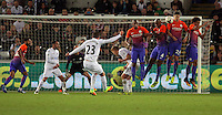 Gylfi Sigurdsson of Swansea City takes a free kick which is deflected by John Stones of Manchester City during the EFL Cup Third Round match between Swansea City and Manchester City at The Liberty Stadium in Swansea, Wales, UK. Wednesday 21 September.