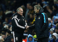Swansea City caretaker manager Alan Curtis shakes hands with Manchester City manager Manuel Pellegrini at the end of the game during the Barclays Premier League match between Manchester City and Swansea City played at the Etihad Stadium, Manchester on December 12th 2015