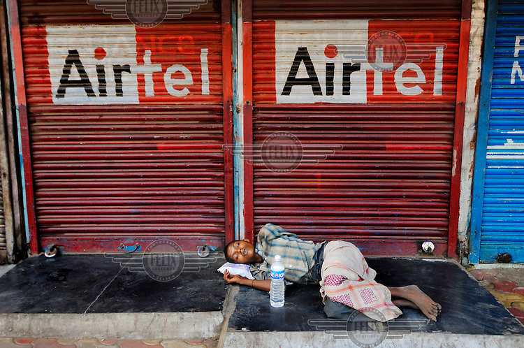 Homeless woman in front of a closed shop decorated with advertising for Airtel mobile phone network.