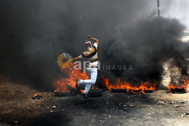 A Palestinian protester throws stones at an Israeli soldiers during clashes in the northern West Bank village of Kufr Qaddum, after the weekly protest against the expansion of the nearby Jewish settlement of Kdumim, on May 25, 2012. Photo by Nedal Eshtayah