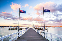 Russell Pier at sunset with New Zealand flag, Bay of Islands, Northland Region, North Island, New Zealand