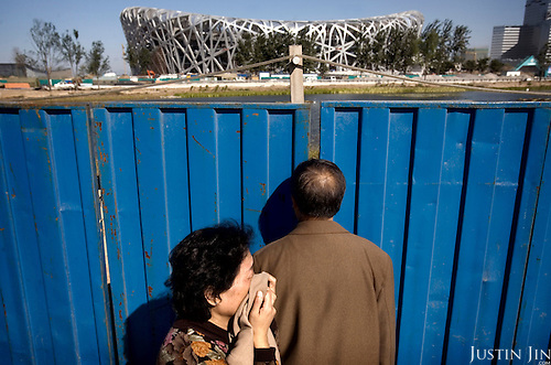 "A passer-by covers herself from dust as she walks past the ""Bird's Nest"" National Stadium, which will be unveiled for the 2008 Summer Olympics. Beijing is one of the most air-polluted cities on earth."