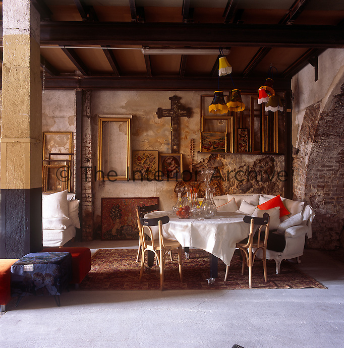 A country dining room with distressed stone walls and a beamed ceiling. A sofa and chairs are set around a round dining table.