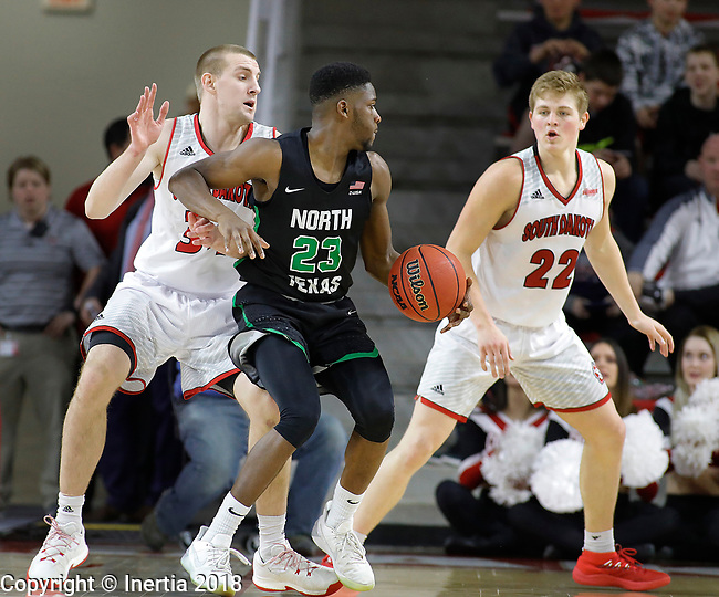 VERMILLION, SD: MARCH 14:  Michael Miller #23 of North Texas dribbles toward South Dakota defenders Nick Fuller #34 and Tyler Peterson #22 during the 2018 CBI Basketball Tournament at the Sanford Coyote Sports Center in Vermillion, S.D.  (Photo by DIck Carlson/Inertia)