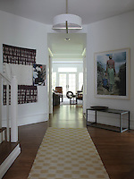 View of the living room from the entrance hall where a large photograph of an African woman hangs opposite   an African fabric and painting