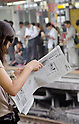 Tokyo, Japan - A Japanese woman reads the newpaper at Shinjuku Station. Morning commuters typically spend over one hour on the train going to work. Trains are usually so packed that train platform staff have to push commuters to fit in the train so that the doors can close shut. (Photo by Yumeto Yamazaki/AFLO)
