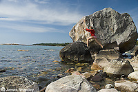 Young girl jumping across rocks on a lakeshore