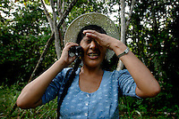 Apolonia Sanchez wipes sweat from her eyes while struggling to recieve cell phone service in the middle of her Chaco, or coca farm, in the jungle inside the Chaparé region of Bolivia. Sanchez, who has fought with Leonilda Zurita for women's rights in the coca production movement, says that while it is easier to grow coca after Evo Morales won presidency, the market is still not overly prosperous. She has had to open a childrens clothing stand near her home in Eterezama to bring in extra money for her family.