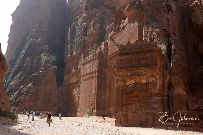 The Street of Facades with their huge monuments carved deep into the red rock. Visitors are dwarfed by the size of the place.<br />
