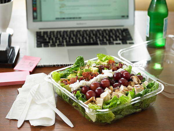 Lettuce salad with chicken breast, grapes, feta, bacon, and avocado in a clear platic to-go container. On a desk with laptop, office supplies, bottle of water.