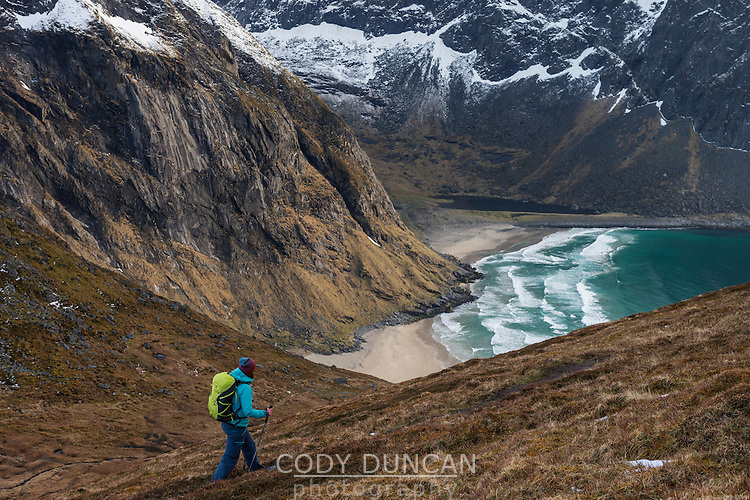 Female hiker with view over Kvalvika beach on trail to Ryten, Moskenesøy, Lofoten Islands, Norway