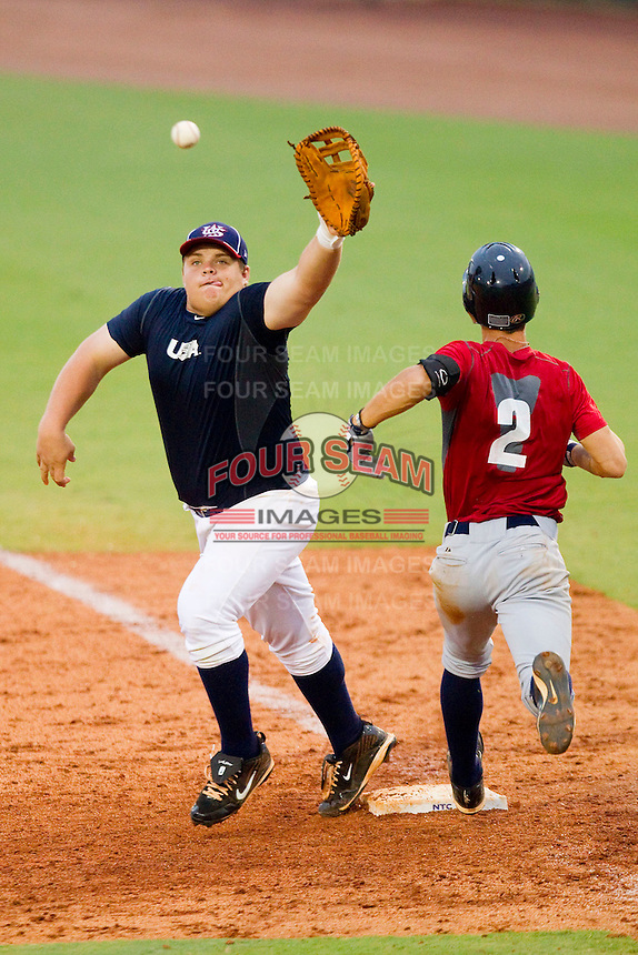 First baseman Dan Vogelbach #59 of Team Blue stretches for a throw as Michael Lorenzen #2 of Team Red hustles down the line during the USA Baseball 18U National Team Trials at the USA Baseball National Training Center on June 30, 2010, in Cary, North Carolina.  Photo by Brian Westerholt / Four Seam Images