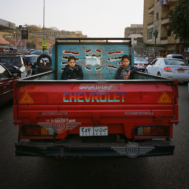 A pair of twins sit in the back of a truck as the driver manoeuvres through traffic in downtown Cairo.