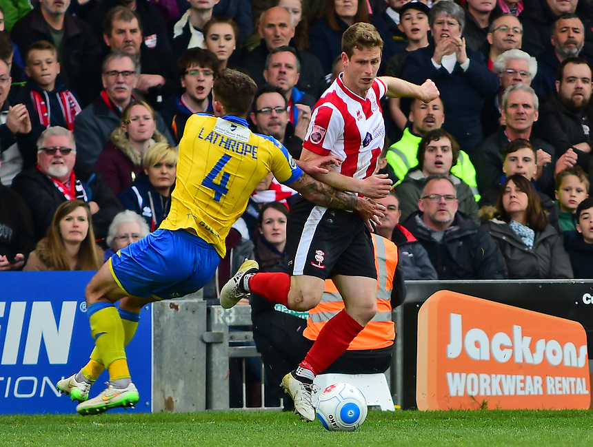 Lincoln City's Adam Marriott vies for possession with Torquay United's Damon Lathrope<br /> <br /> Photographer Andrew Vaughan/CameraSport<br /> <br /> Vanarama National League - Lincoln City v Torquay United - Friday 14th April 2016  - Sincil Bank - Lincoln<br /> <br /> World Copyright &copy; 2017 CameraSport. All rights reserved. 43 Linden Ave. Countesthorpe. Leicester. England. LE8 5PG - Tel: +44 (0) 116 277 4147 - admin@camerasport.com - www.camerasport.com