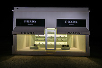 Prada Marfa is  a permant display which is located in Valentine Texas which is about 30 miles from Marfa. It is an unique display since it sit along side the road without anything nearby by artist Elmgreen and Dragset.  All the shoes are right only and the purses have no bottoms.