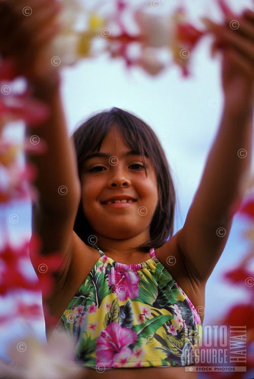 Young girl offering a pink and white Plumeria lei