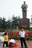 Visitors kowtow to a statue of Mao Zedong at the Statue Square near Mao's birthplace in Shaoshan, Hunan Province, China on 12 August 2009.